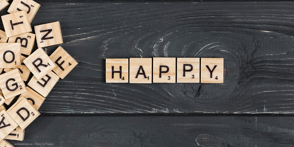 Scrabble tiles spell out the word 'happy'