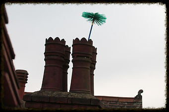Traditional brush coming out of an open chimney pot