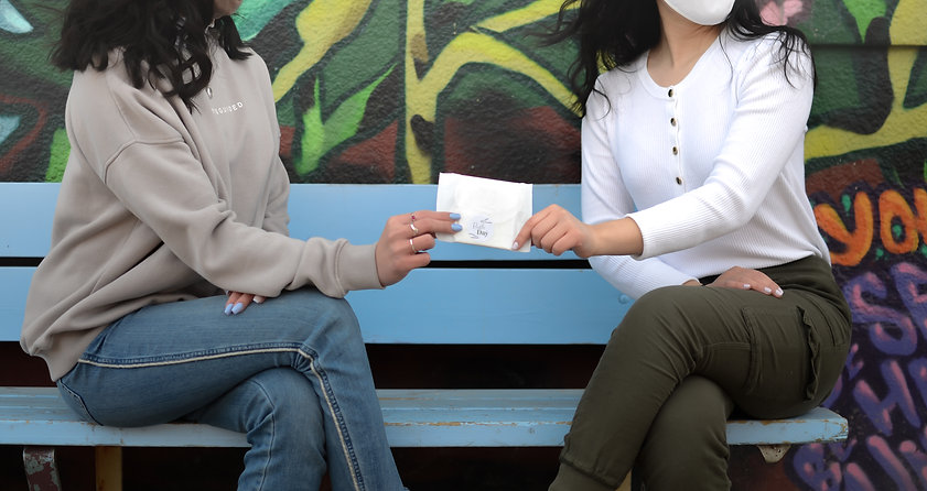 A woman handing a Ruth pad to another woman