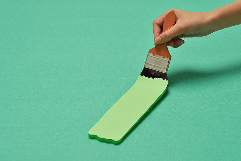 main tenant un pinceau avec de la peinture verte