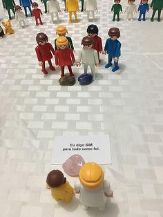 """Na imagem aparece um exemplo de uma constelação com bonecos e as cartas Falas Sistêmics - 2 bonecos (1 criança e outro adulto, representando a mesma pessoa em suas duas fases) de frente para outros 2 que representam seus pais (e outros ancestrais) e a carta de cura que saiu foi """"Eu digo SIM para tudo como foi."""""""