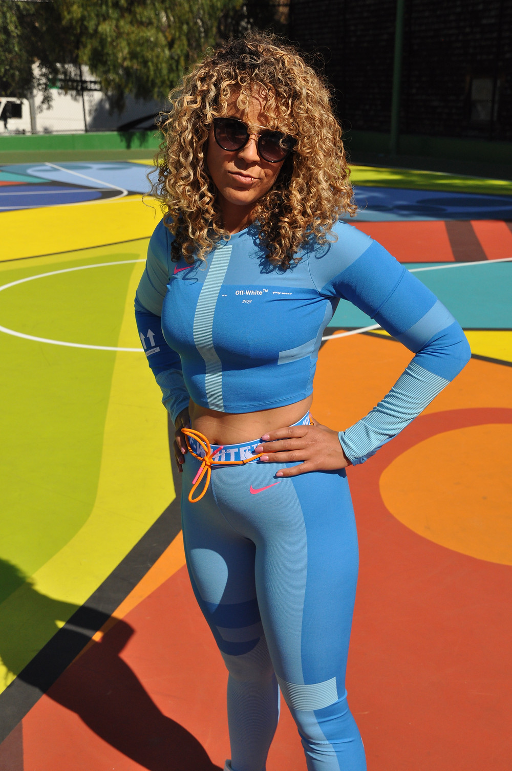 Girl in sunglasses and off white outfit posed on a colorful basketball court