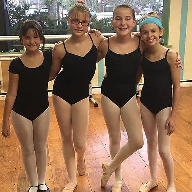 four ballerinas dressed for their dance lesson