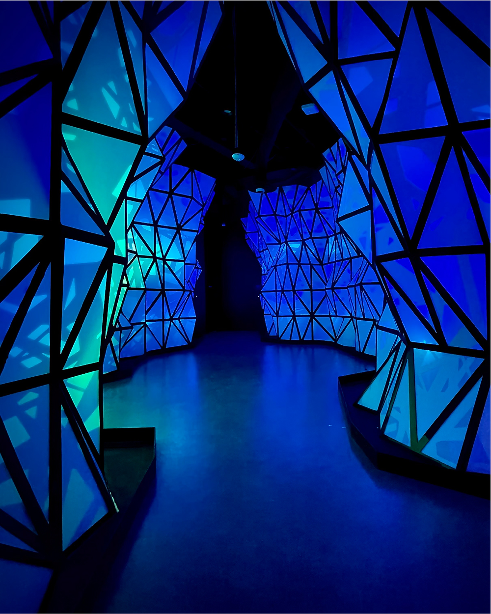 An art installation entitled: UPLOAD_GHOST_S in Omega Mart, Las Vegas; a hallway filled with color-changing LED panels,