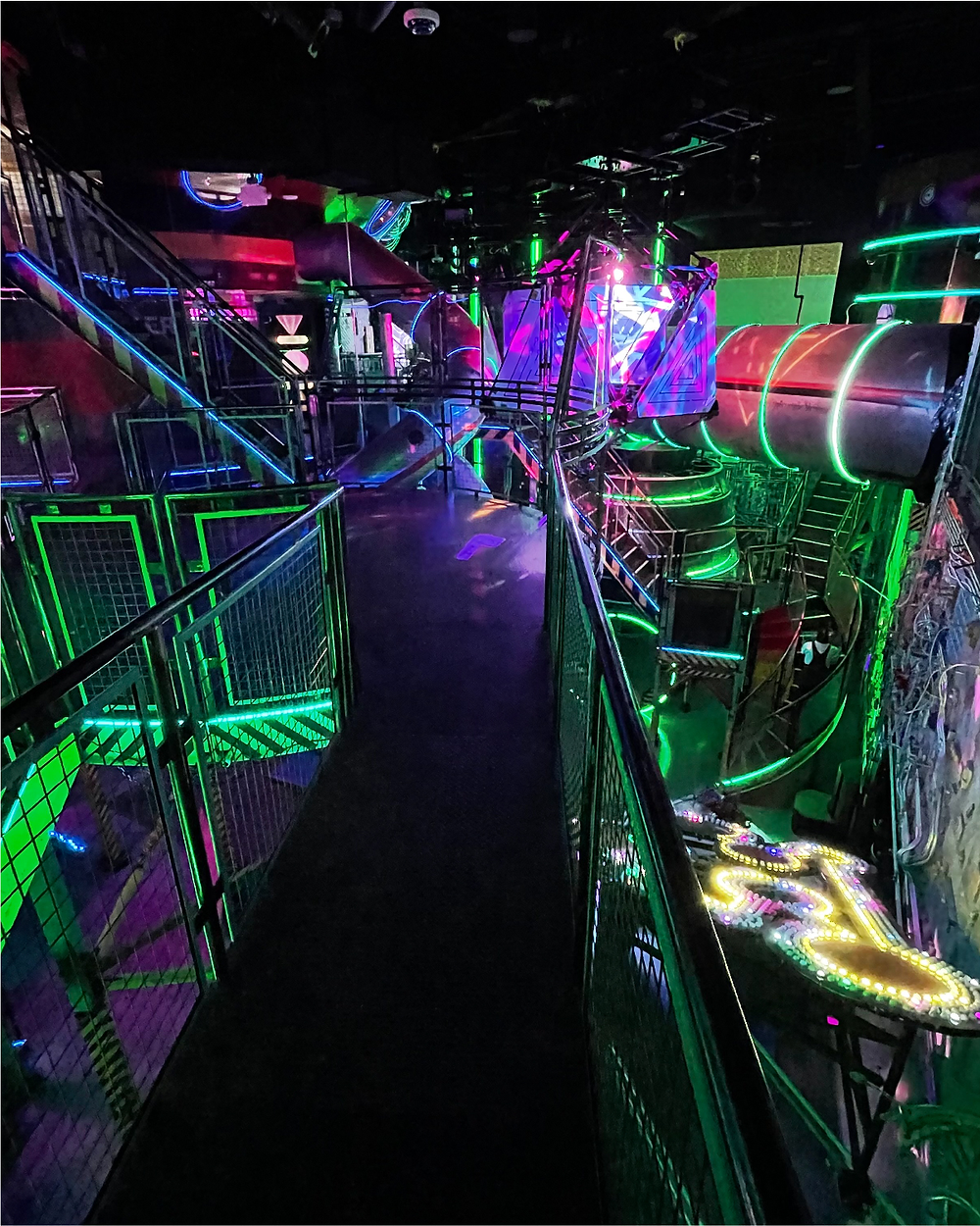 At Omega Mart Las Vegas, double helix slides and several levels of stairs wind around one another; green lighting irradiates it all as immersive adventure lurks around every corner.
