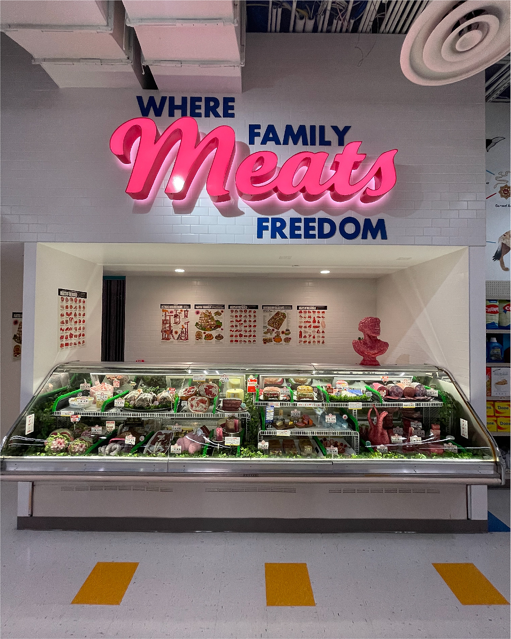"""A supermarket deli counter; a sign above the counter says, """"Where Family Meats Freedom"""" in bright pink-and-blue text. Inside the deli case, mysterious shapes occupy the places where meat would normally live."""