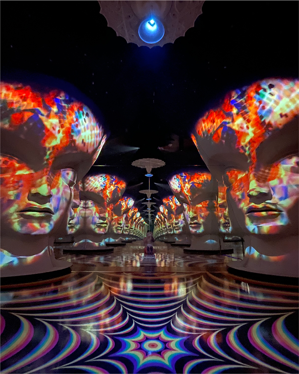 An exhibit at Meow Wolf Omega Mart, featuring a series of psychedelic faces projected mapped onto walls.
