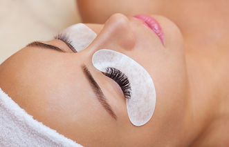 Beautiful Woman with long eyelashes in a beauty salon. Eyelash extension procedure.jpg