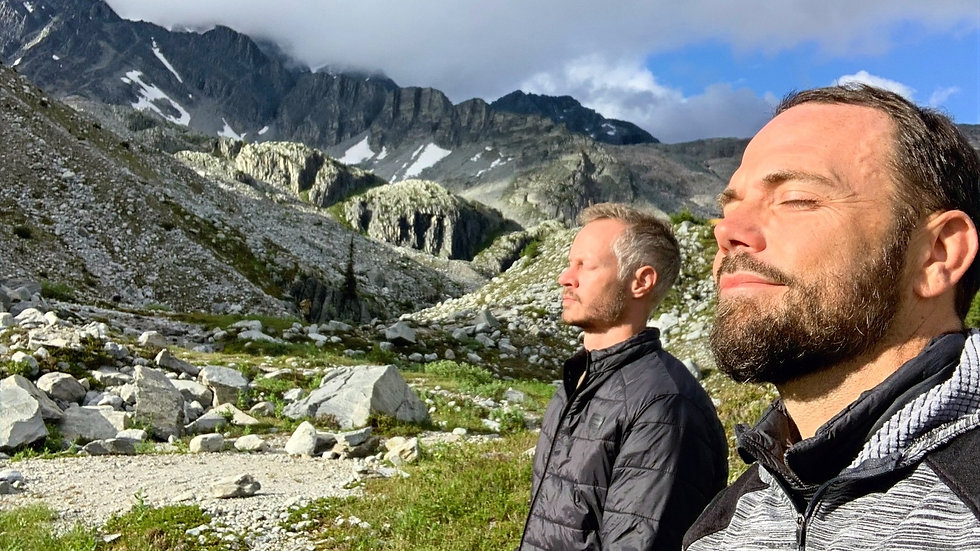 Men's life coach meditation support on top of a mountain