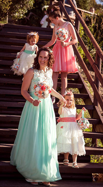 bridesmaid mother with young children walking down stairs in sun
