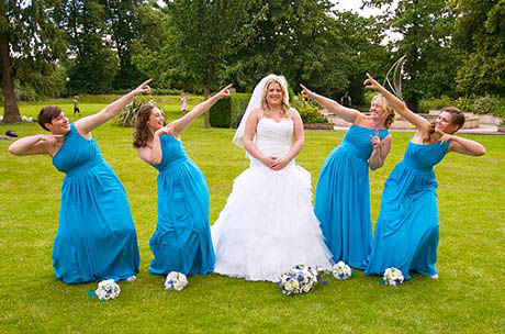 bride in designer dress on grass with four blue bridesmaids pointing for photograph