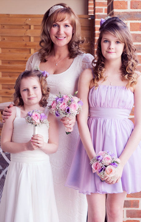 smiling bride with two young girls as bridesmaids purple dress flower bouquets