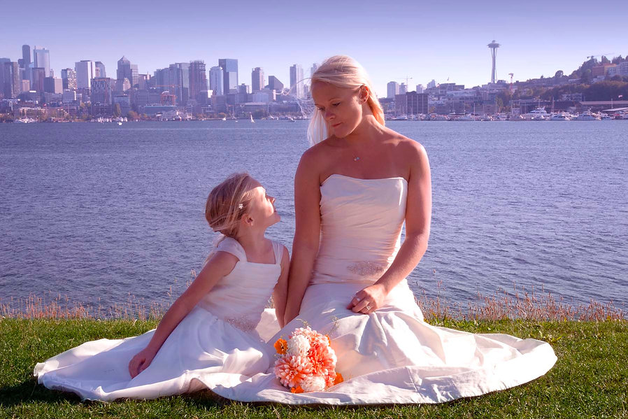 bride and bridesmaid Seattle sitting on grass by water