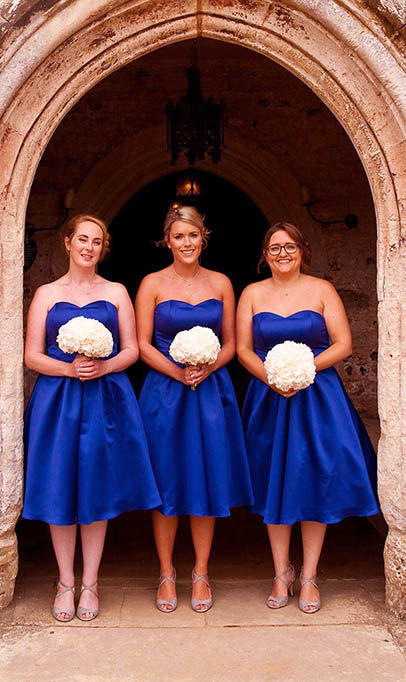 three bridesmaids in blue dresses with white flowers under church arch entrance
