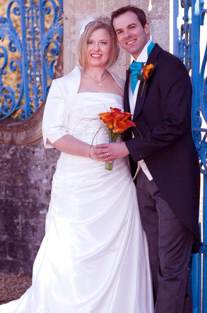 bride in white bespoke wedng gown with veil orange flowers and groom with blue tie