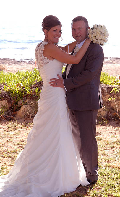 wedding photo on beach embracing bride and groom
