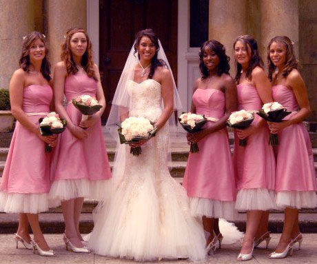 bride and bridesmaids in pink dresses bouquets of white flowers