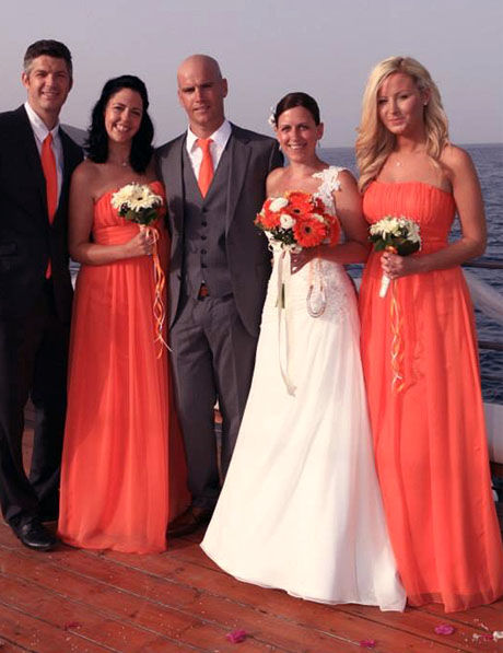 orange bridesmaids dresses and white bridal dress on boat groom in grey suit orange tie