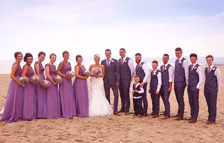 group photograph of bridesmaids in purple dresses with bride and groom and page boys on beach