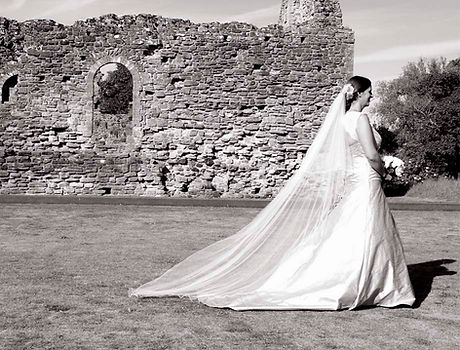 bespoke veils bride walking in front of castle wall ruins