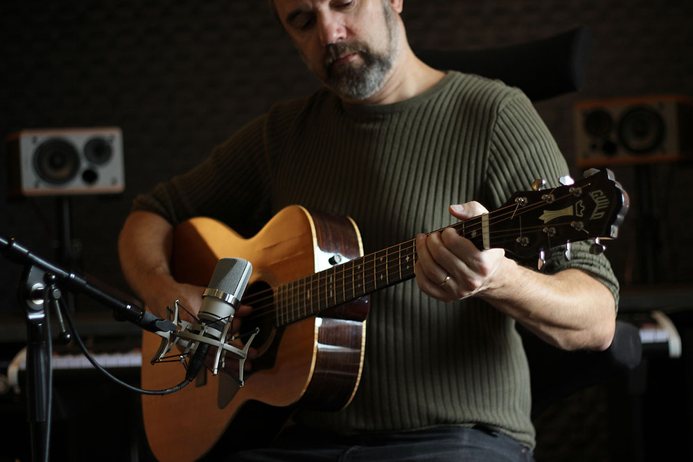 Marcos Ciscar playing fingerpicked guitar in his studio