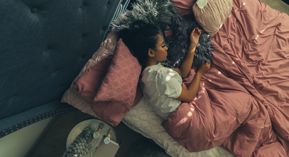 Woman laying in bed on her side, eyes close with blankets up to her waist. 2 pill bottles on her night stand.