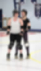 Two skaters laugh together during a practice