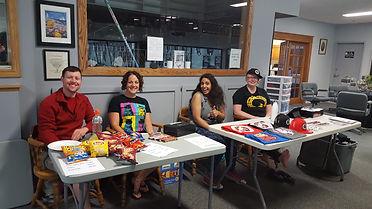 Volunteers sit behind tables selling merchandise and snacks