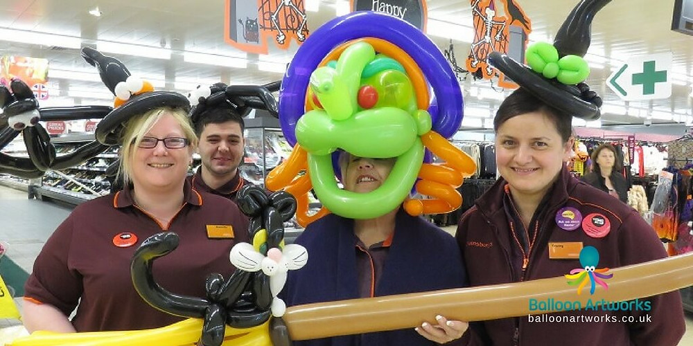 Staff from Sainsbury's Ripley store dressed in Halloween balloon hats and a giant balloon witch mask by Balloon Artworks, the Derbyshire Balloon Artist