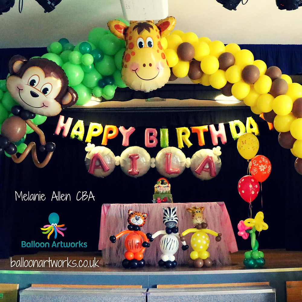 Amazing jungle theme balloon arch for a first birthday party with monkey and giraffe balloon by Balloon Artworks, Ripley Derbyshire