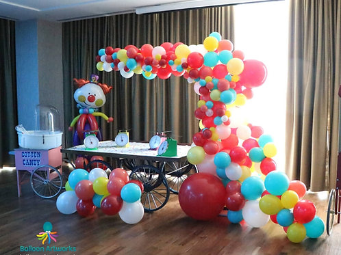 Circus theme organic balloon arch with clown character