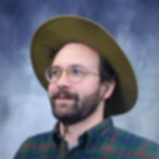 "PICTURED HERE: the artist, Erik Pedersen, in flannel shirt, park ranger hat, and round wire-framed glasses he bought at Target because his roommates told him they were flattering back in 2017 when he needed a boost. He has a short beard and and unkempt brown hair sticking out from under the wide-brimmed hat. He's a little sunburnt (oops) and there's a sort of cloudy blue-grey backdrop behind him, like they use for yearbook photos in K-12. Don't even get me started on his expression. If his grandmother saw it, she would say ""smile a real smile!"""