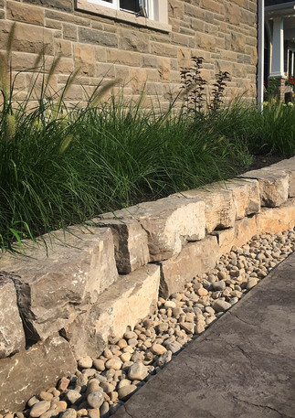 Armour Stone Garden Retaining Wall lined with River Rock