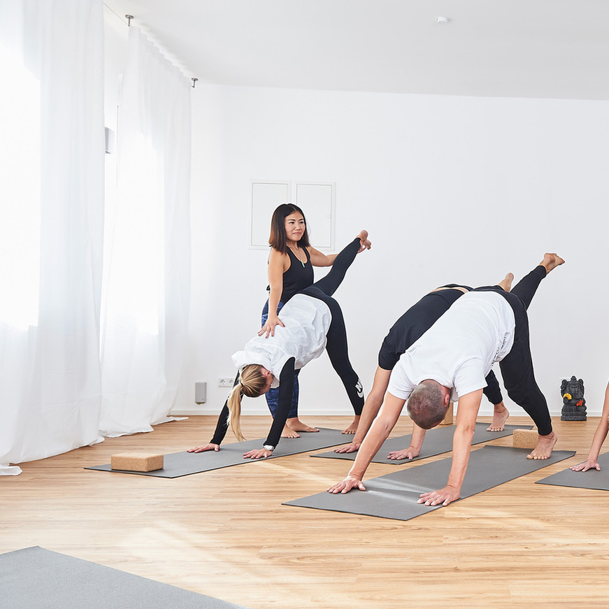 Assisting participants in a yoga class