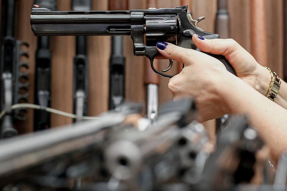 mulher segurando arma de fogo