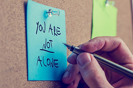 A person writing on a blue post-it note. The text reads, You Are Not Alone.
