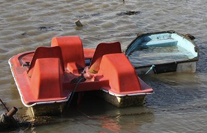 A pedalo, a scruffy red seaside pedal boat and a blue rowing boat filled with water tied together