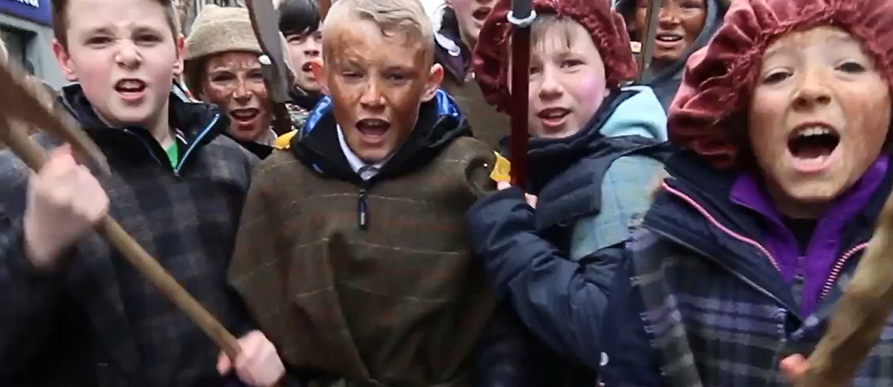 Children with fake weapons charging in historical reenactment at the Border reviews Festival in Hawick Scotland