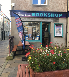 Customer entering The Shetland Times Bookshop, a raised bed of flowers in the foreground