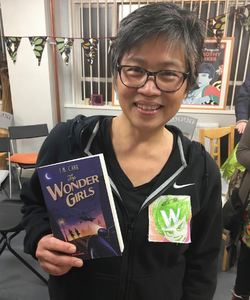 Children's author holding a copy of The Wonder Girls and wearing a fabric W badgeCandy Gourlay