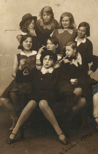 A sepia photo from 1930  of a 'Bugsy Malone' style gang of eight girls
