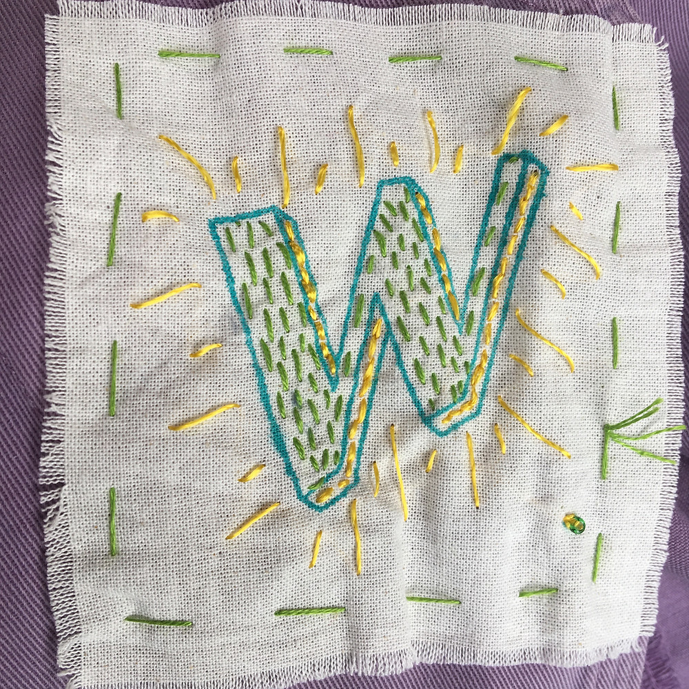 A letter w embroidered on a small piece of cloth to make a badge,