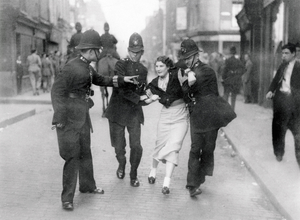 A young woman struggling against arrest by 2 uniformed police during The Battle of Cable Street