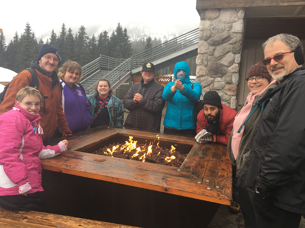 A group of people enjoys a fire pit.