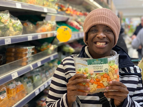 Girl smiling in supermarket with vegatable soup kit