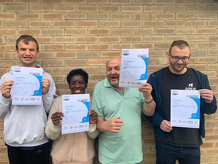 Four people holding certificates