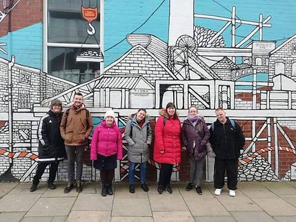 Group of people in Sheffield infront of artwork on wall
