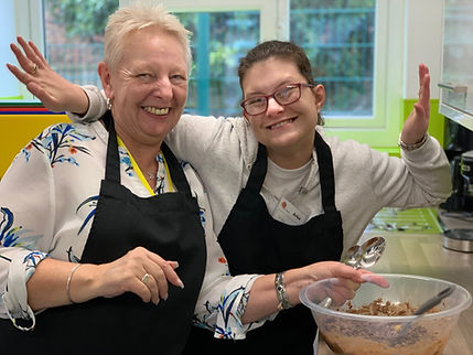 Two women baking with aprons on