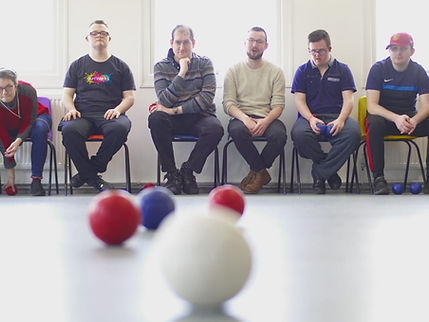 Artists playing boccia, red, blue and white balls on the floor