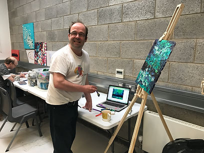 Tim holding sponge brush infront of easel with textured green painting